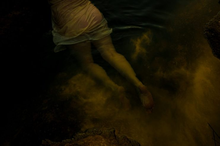A woman's torso and legs covered by a sheer dress swimming in water