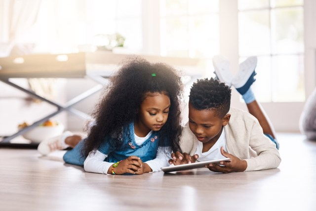 african-american boy and girl lying on the floor while looking at a tablet device