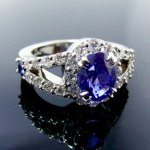 Oval sapphire and diamond halo engagement ring in platinum