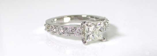 A custom designed engagement ring with a princess cut diamond center and round cut diamond side stones
