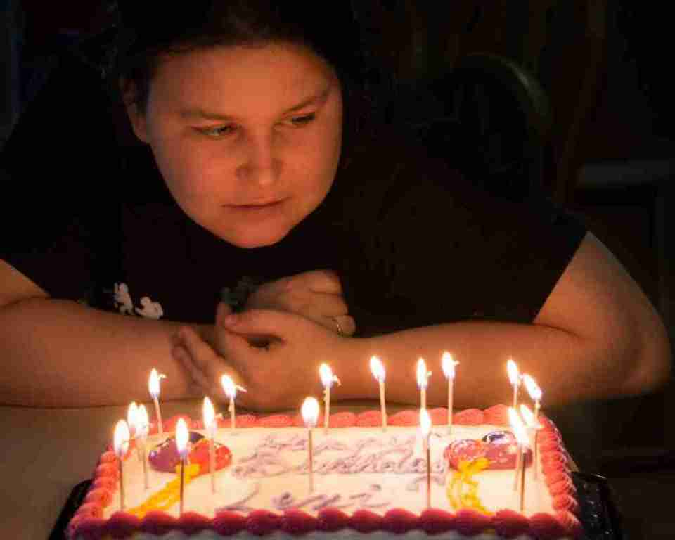 Photo of a girl blowing out birthday candles using night photography settings