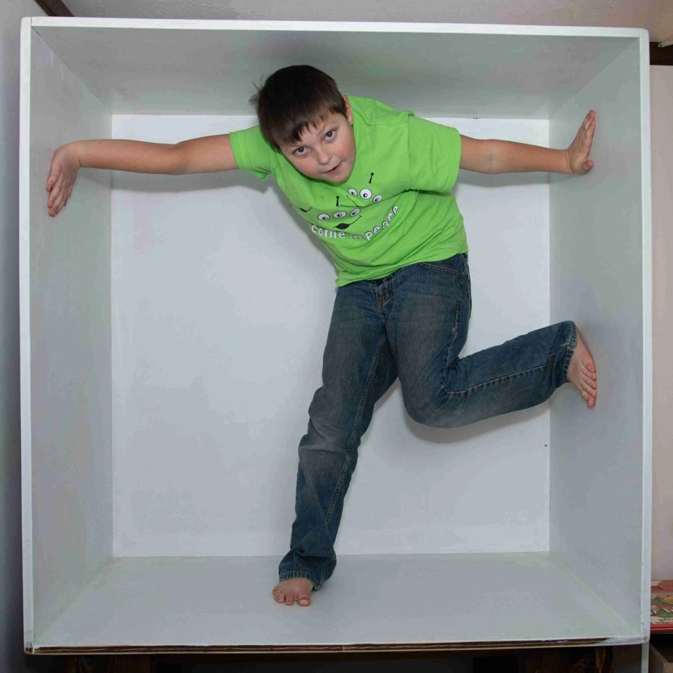 A boy using his whole body to fill the box