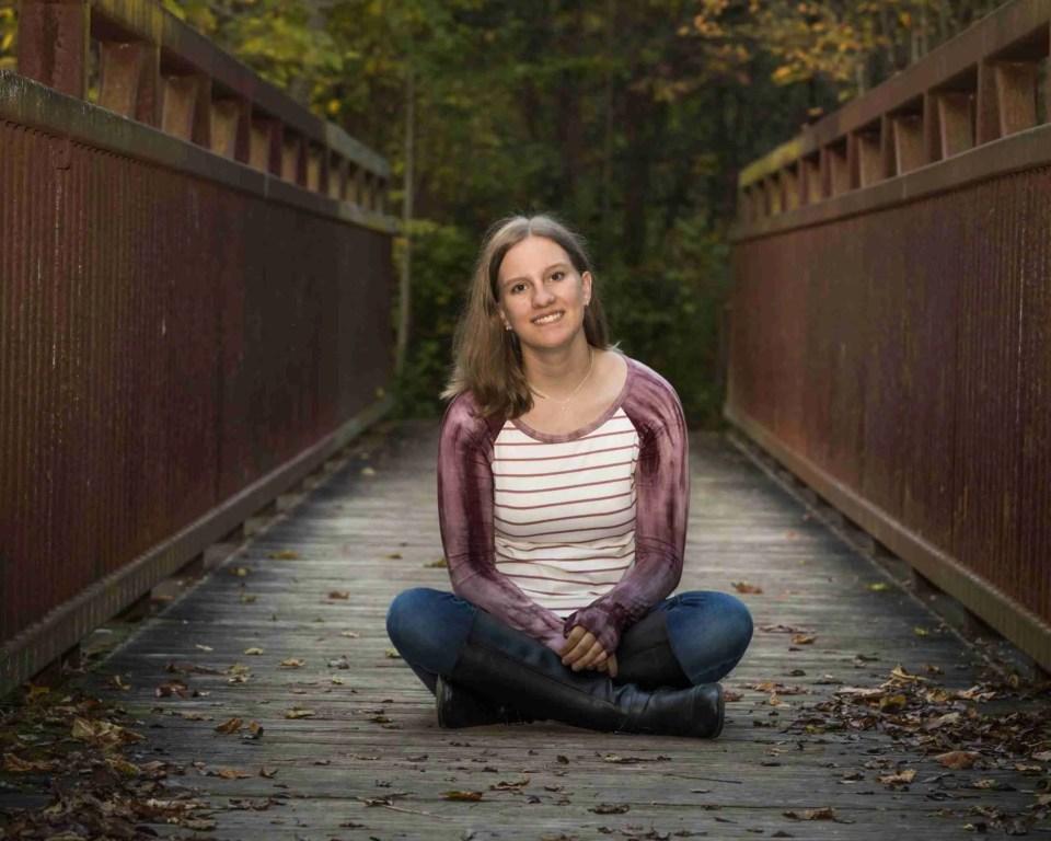 Senior girl sitting on the middle of a bridge