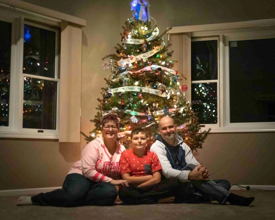 Author with husband and son in front of Christmas Tree at new home