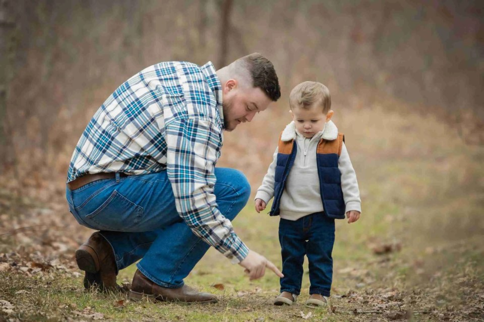 little boy and dad searching the ground using the search for treasure photography prompt for families