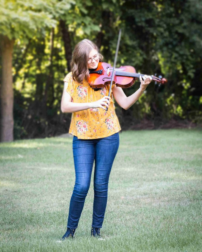A girl plays her violin in nature