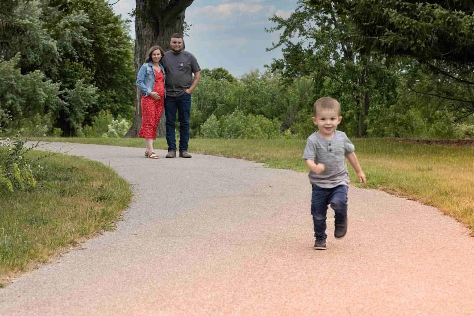 a toddler runs away from parents toward the photographer
