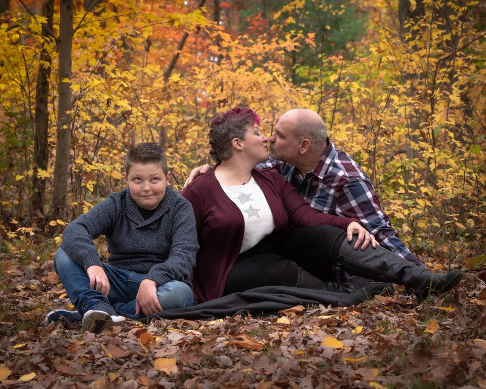 autumn photoshoot with preteen rolling his eyes at parents' kiss