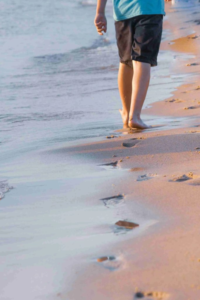 A boy's feet walking along a beach waterline