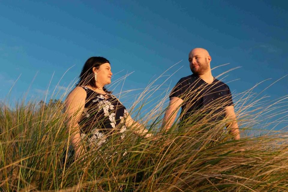 a couple holds hands amongst the beach grass