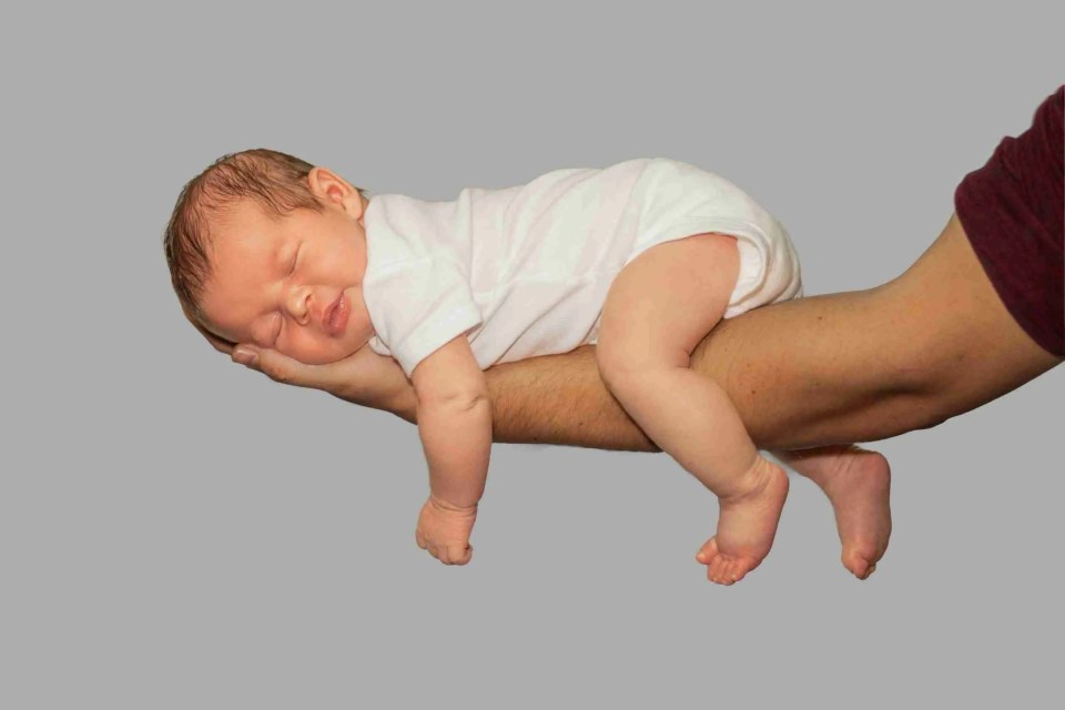 an infant laying across dad's arm