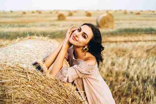 a closeup portrait of a woman leaning on a hay bale for an autumn photoshoot