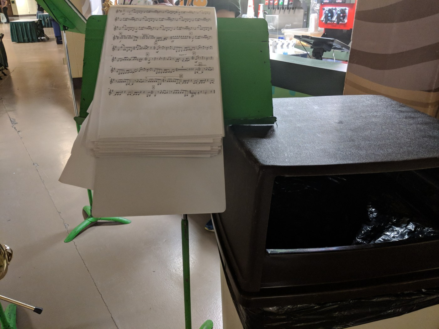 a binder dangling over a music stand that is supported by a trash can