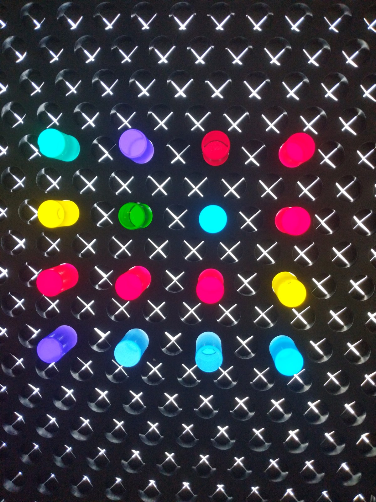 A black wall with sixteen colored light sticks that form a square
