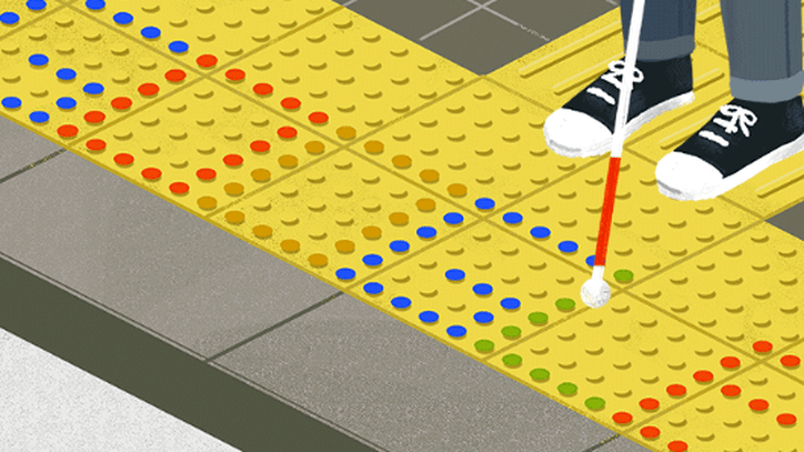 A person wearing black shoes stands with a red and white cane on yellow dotted tactile pavement. Some dots are different colors and spell out Google