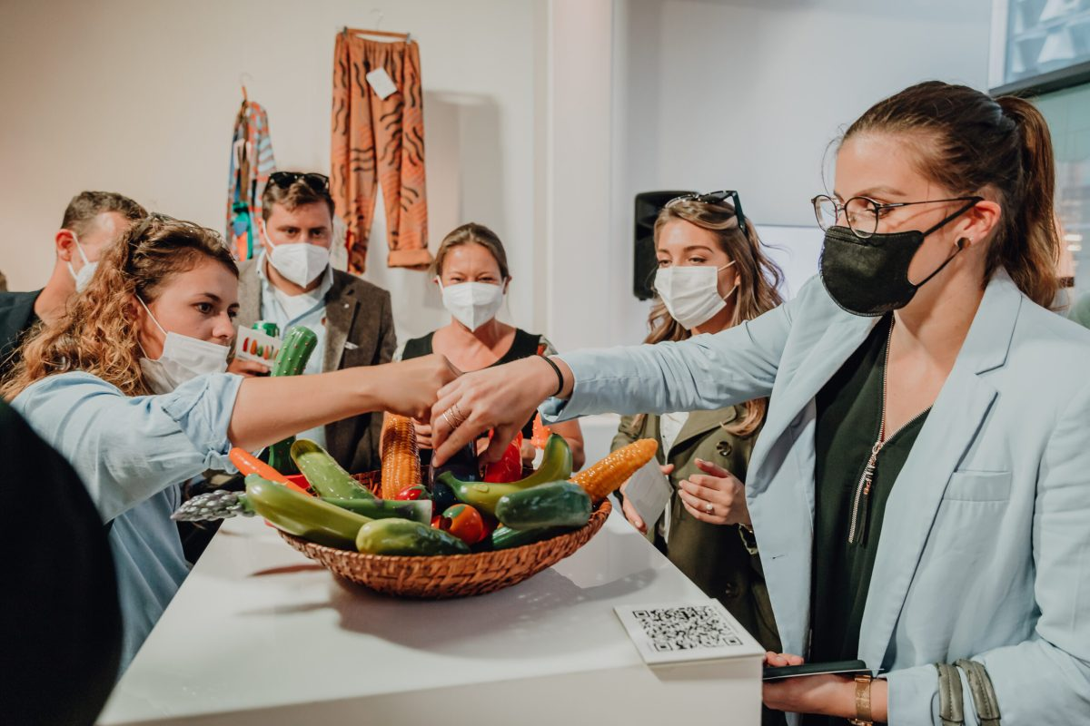 Menschen schauen einen Korb Gemüse an. Das Gemüse wie Gurke, Mais und Möhre ist aus Silikon , es sind Dildos