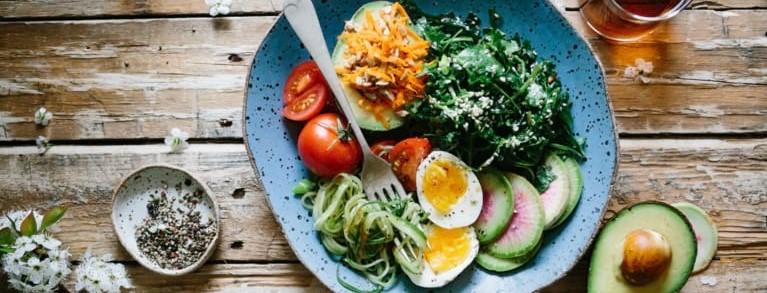 Assiette d'aliments sains, avocat, tomates, betteraves crues, oeuf