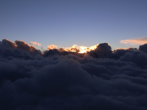 THe sun sets in a sea of afternoon cloud