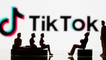 Силуэты людей на фоне логотипа ТикТок