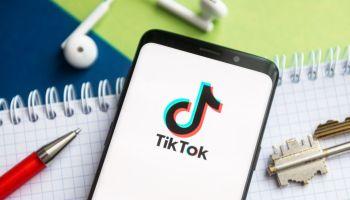Лого ТикТока на смартфоне, лежащем на тетради рядом с ручкой, ключами и наушниками