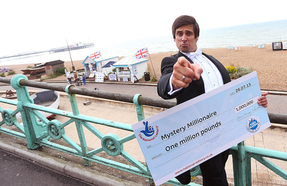 brighton photographers with a butler and a lottery cheque point at them
