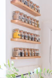 wood floating shelves for condiment storage in a kitchen