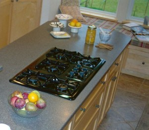 black 5 burner gas cooktop with intuitive control knobs on island