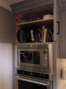 storage accessories in deep cabinet above ovens