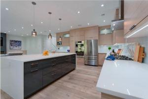 dark kitchen island with light perimeter cabinets