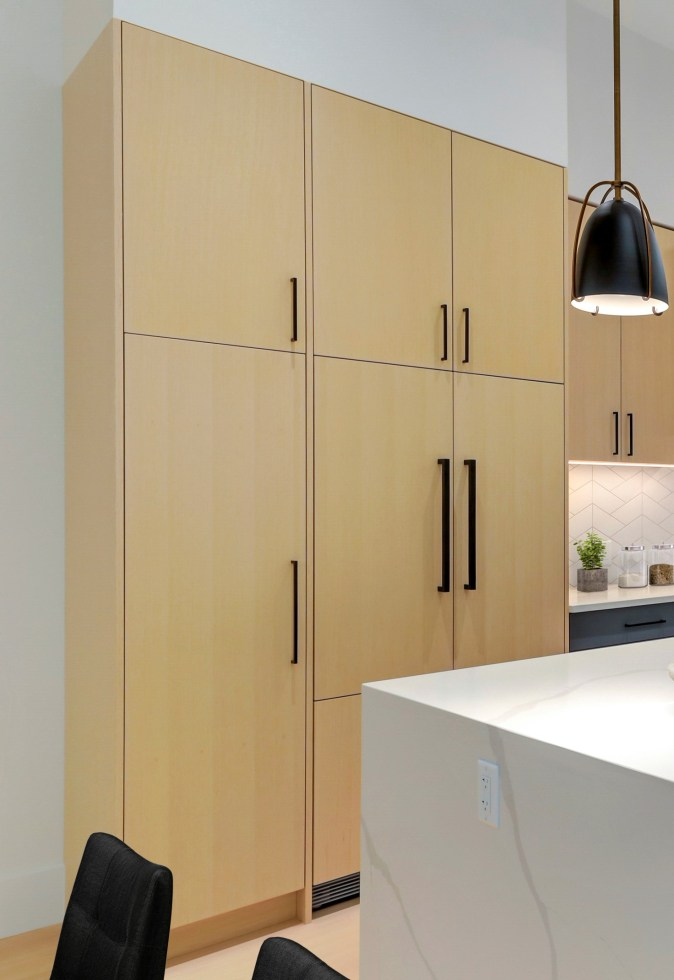 light wood paneled fridge and pantry