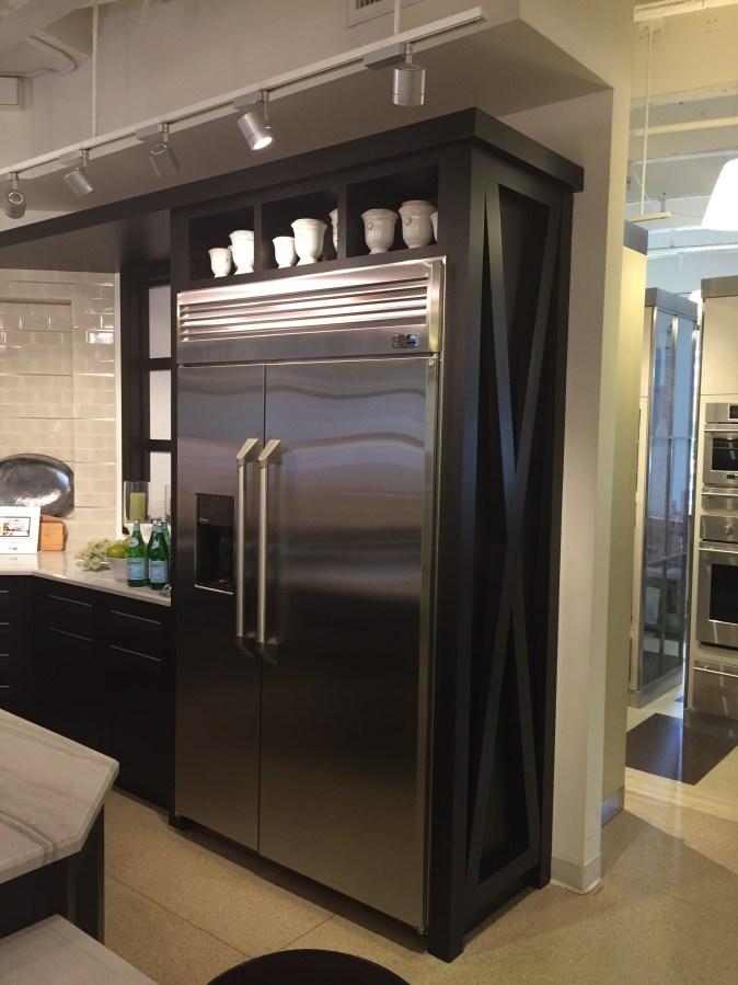 divided open shelves above fridge