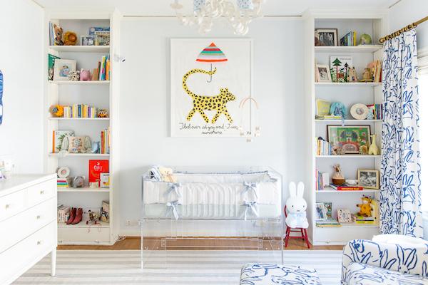quarto de bebe com paredes brancas e detalhes em azul