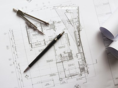 byggetegning av nytt bygg med passer og blyant