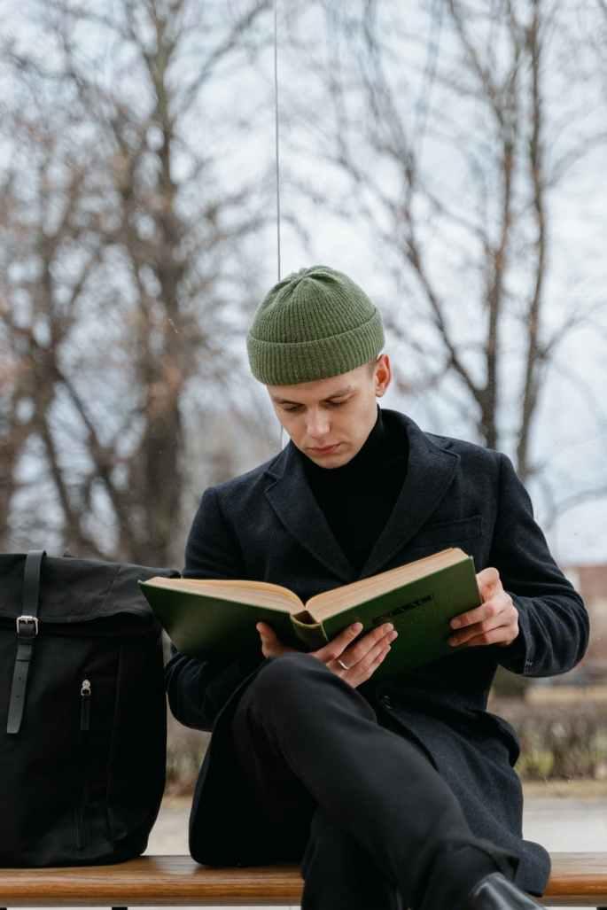 a man wearing a green bonnet reading a book
