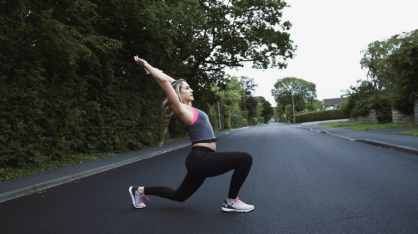 Fitness girl warms up before exercising on the street