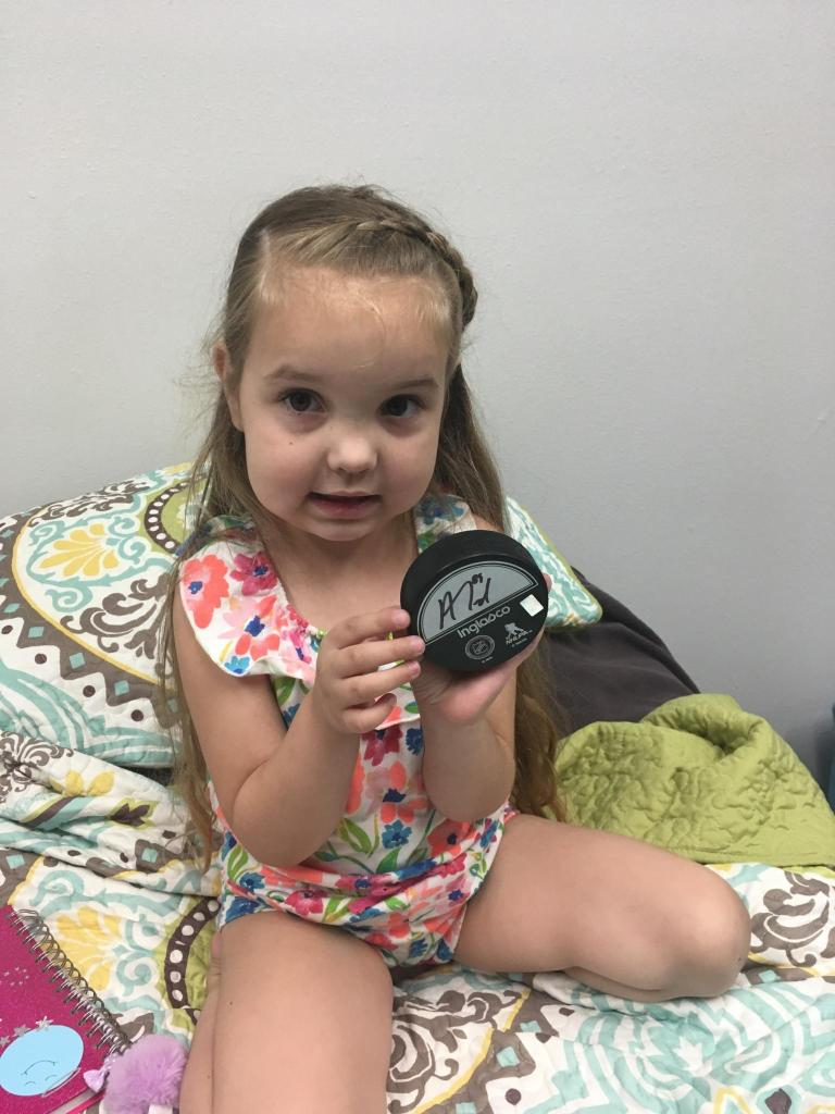 Cami, donning her blue, pink, and green floral outfit, poses for the camera with a hockey puck signed by #89 on the Vegas Golden Knights, Alex Tuch.
