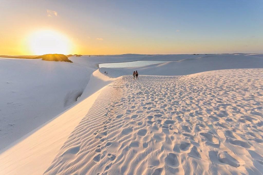 pôr do sol ao fundo e dunas nos lençóis maranhenses