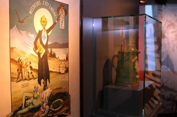 """Cartaz """"A morte da Fada Verde"""" na Guguss, revista semanal publicada por Louis Bron, satiriza a proibição do consumo de absinto na Suíça. No canto superior à direita, calendário marca dia e horário da entrada em vigor da nova regra (foto: Eduardo Vessoni)"""