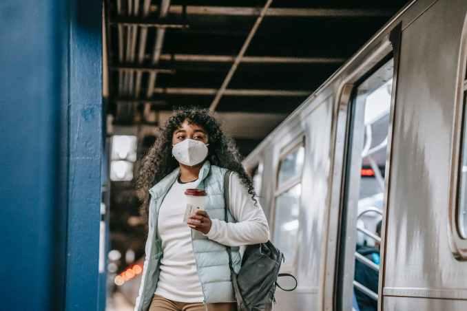 black woman in mask leaving metro train