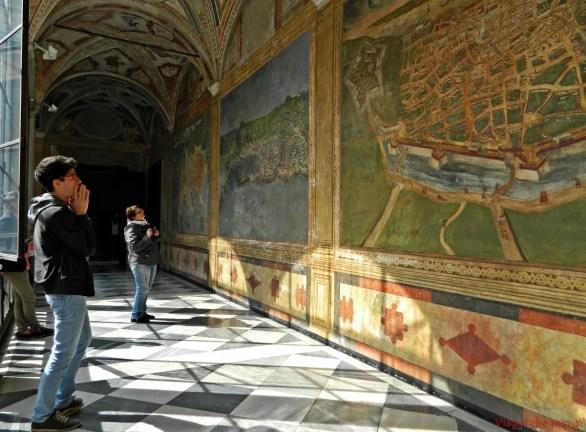 Visitatori osservano le mappe dipinte sui muri del Palazzo della Prefettura di Genova.