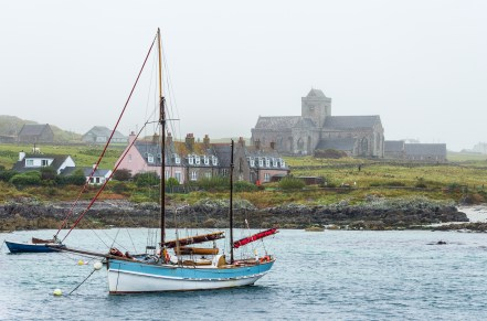 IONA, ARGYLL, SCOTLAND - SEPTEMBER 25, 2014: vintage schooner sailboat with furled sails moored at the isle natural port looking Mull. Fog, evocative atmosphere wraps the touristic medieval Iona Abbey COMERCIAL: Vintage schooner sailboat with furled sails moored at Iona island natural port close to Mull, in the Inner Hebrides of Scotland. Foggy, evocative atmosphere wraps the touristic medieval Iona Abbey.