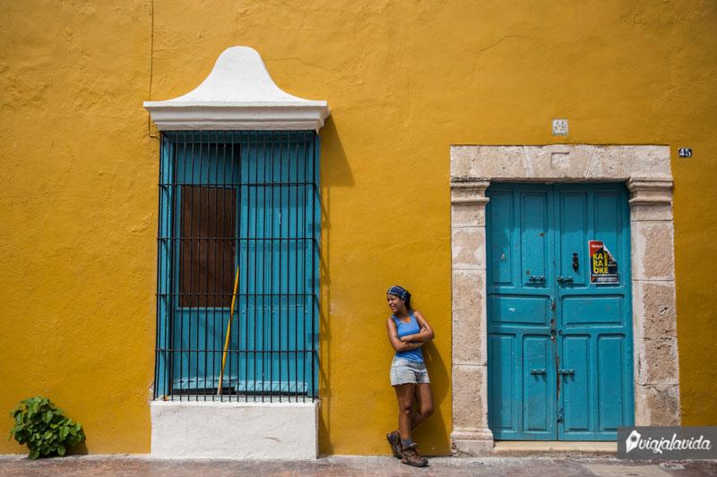 Mujer posando frente a pintoresca casa amarilla.