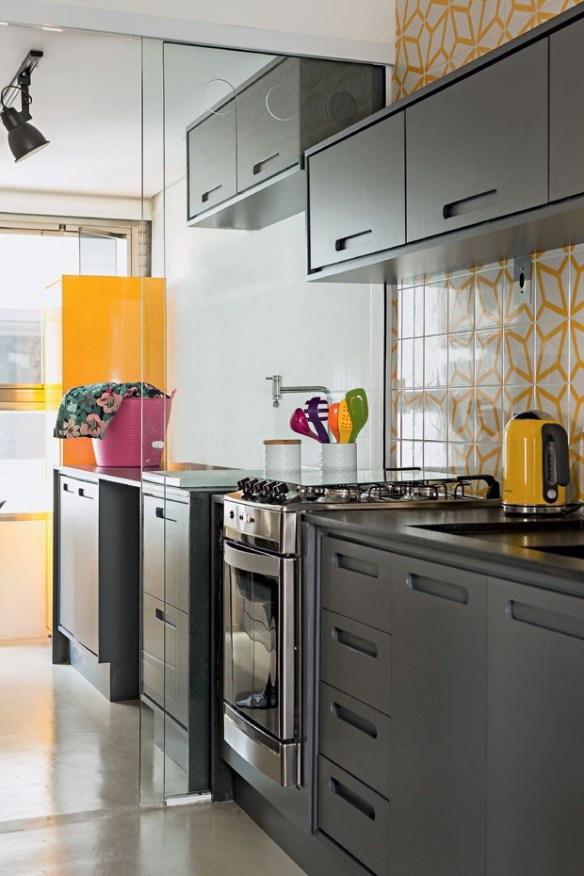 dividir cozinha lavanderia area de servico porta vidro incolor cozinha armarios grafite detalhes amarelos revestimento azulejo piso cimento queimado