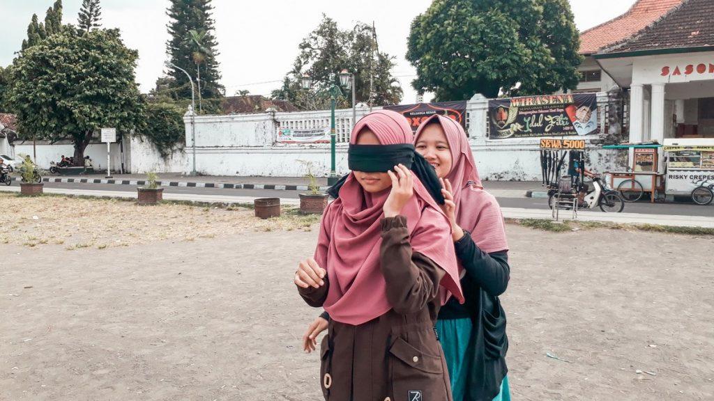 Chica comprobando la leyenda del parque Alun Alun de Yogyakarta