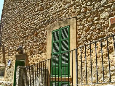 Fachada piedra ventana verde Deià