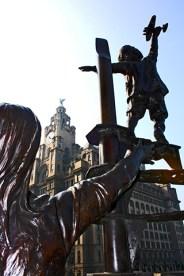 Escultura migración mujer niño avión puerto Liverpool
