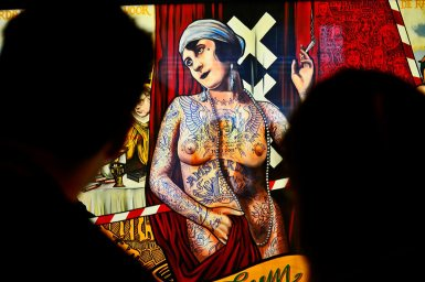 Pareja mirando mural mujer tatuajes rebelde fumando marihuana Amsterdams Historich Museum