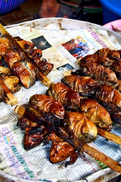 Pincho moruno ranas parrilla mercado sobre la vía del tren Mae Klong