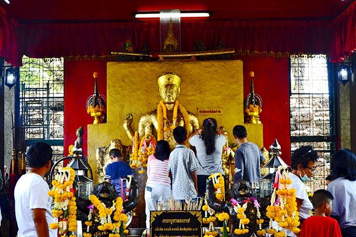 Fieles buda dorado adornos flores templo Phra Kan Shrine Lopburi