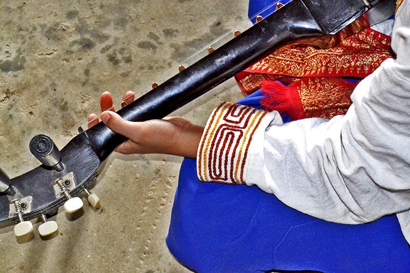 Niño tocando guitarra Casa Negra Chiang Rai